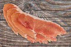 Φέτες Prosciutto στο παλαιό ξύλινο υπόβαθρο Στοκ φωτογραφία με δικαίωμα ελεύθερης χρήσης