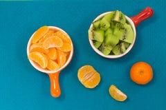 Φέτες tangerine στο κόκκινο κεραμικό πιάτο Φέτες του ακτινίδιου Στοκ Φωτογραφίες