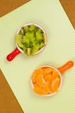 Φέτες tangerine στο κόκκινο φλυτζάνι Φέτες των φρούτων ακτινίδιων στο πορτοκαλί φλυτζάνι Στοκ Εικόνες