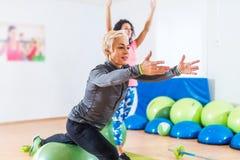 Φίλαθλες γυναίκες που κάνουν τις τεντώνοντας ασκήσεις με τη σφαίρα σταθερότητας ικανότητας σε μια αθλητική λέσχη στοκ εικόνα με δικαίωμα ελεύθερης χρήσης