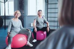 Φίλαθλες συνταξιούχες κυρίες που κάθονται στις σφαίρες ικανότητας εκπαιδευτικές Στοκ φωτογραφία με δικαίωμα ελεύθερης χρήσης