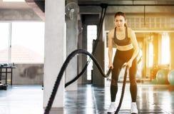 Φίλαθλη και λεπτή ασιατική γυναίκα που χρησιμοποιεί το σχοινί μάχης στη γυμναστική, θηλυκή να κάνει άσκηση στο λειτουργικό traini στοκ φωτογραφία