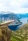 Φίλαθλη τοποθέτηση γυναικών σε Trolltunga Νορβηγία Στοκ εικόνες με δικαίωμα ελεύθερης χρήσης
