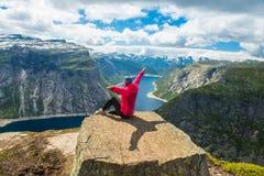 Φίλαθλη τοποθέτηση γυναικών σε Trolltunga Νορβηγία Στοκ Εικόνα