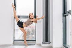 Φίλαθλος που κάνει τις ασκήσεις με αυξημένος ένα πόδι που εξετάζει τη κάμερα στοκ φωτογραφία με δικαίωμα ελεύθερης χρήσης