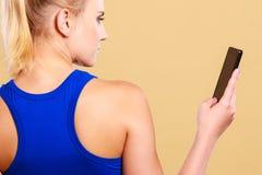 Φίλαθλος που χρησιμοποιεί το κινητό τηλέφωνο στη γυμναστική Στοκ Φωτογραφίες