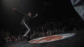 Φίλαθλος χαριτωμένος τύπος στα μαύρα ενδύματα που δυναμικά στη σκηνή φεστιβάλ απόθεμα βίντεο