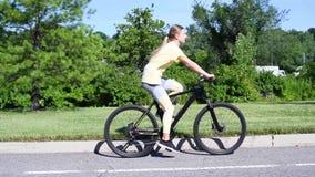 Φίλαθλο νέο οδηγώντας ποδήλατο γυναικών υπαίθριο Ενεργό οδηγώντας ποδήλατο γυναικών στο πάρκο απόθεμα βίντεο