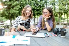 Φίλες με το μπουλντόγκ στον καφέ πάρκων στοκ εικόνες