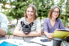 Φίλες με το μπουλντόγκ στον καφέ πάρκων στοκ εικόνα με δικαίωμα ελεύθερης χρήσης