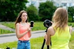 Φίλες μικρών κοριτσιών Το καλοκαίρι στο πάρκο στη φύση Γράφει το βίντεο στη κάμερα Στα χέρια του κρατά το α στοκ φωτογραφία