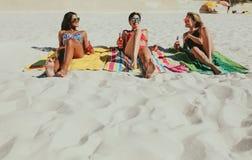 Φίλες που κάνουν ηλιοθεραπεία στην παραλία στοκ φωτογραφία