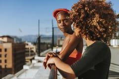 Φίλες που κρεμούν έξω σε μια στέγη Λα στοκ φωτογραφίες