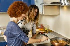 Φίλες που μαγειρεύουν στο σπίτι από κοινού στοκ εικόνα