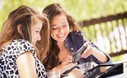 Φίλες που χρησιμοποιούν τον υπολογιστή, την ταμπλέτα και το Smartphone τους στοκ εικόνα