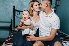 Φίλημα ζευγών αγάπης, η κόρη μωρών τους στις περιτυλίξεις στοκ φωτογραφίες με δικαίωμα ελεύθερης χρήσης