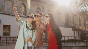 Φίλοι δύο γυναίκες και ένας άνδρας που κάνει selfie στον ήλιο Στα πλαίσια ενός παλαιού κτηρίου απόθεμα βίντεο