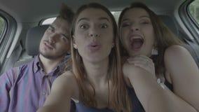 Φίλοι εφήβων που παίρνουν selfie τις φωτογραφίες στο πίσω μέρος της οδήγησης του αυτοκινήτου που χαμογελά και που γύρω από την απ απόθεμα βίντεο