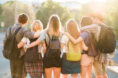 Φίλοι με το αγκάλιασμα σακιδίων πλάτης που περπατά στην πόλη στοκ εικόνα