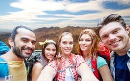 Φίλοι με το σακίδιο πλάτης που παίρνει selfie ove τα βουνά στοκ εικόνες