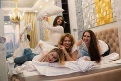 Φίλοι νέων κοριτσιών που παλεύουν τα μαξιλάρια στην κρεβατοκάμαρα στοκ φωτογραφία