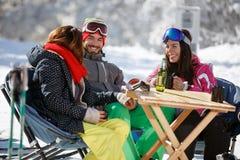 Φίλοι να κάνει σκι μιλώντας και έχοντας τη διασκέδαση στον καφέ Στοκ Εικόνες