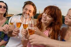 Φίλοι που έχουν το μεγάλο χρόνο στο γιοτ, πίνοντας τη σαμπάνια, χαμόγελο στοκ εικόνα