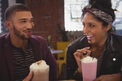 Φίλοι που απολαμβάνουν milkshakes στον καφέ στοκ εικόνες