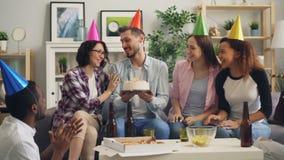 Φίλοι που γιορτάζουν τα φυσώντας κεριά γενεθλίων στο κέικ που πίνει κα απόθεμα βίντεο
