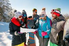 Φίλοι που διαβάζουν έναν χάρτη εγγράφου στις χειμερινές διακοπές στο χιονώδες βουνό Στοκ Εικόνα