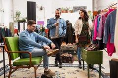 Φίλοι που επιλέγουν τα ενδύματα στο εκλεκτής ποιότητας κατάστημα ιματισμού Στοκ εικόνα με δικαίωμα ελεύθερης χρήσης