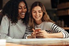 Φίλοι που κάθονται σε έναν καφέ που εξετάζει το κινητό τηλέφωνο Στοκ εικόνα με δικαίωμα ελεύθερης χρήσης