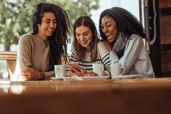 Φίλοι που κάθονται σε έναν καφέ που εξετάζει το κινητό τηλέφωνο Στοκ φωτογραφίες με δικαίωμα ελεύθερης χρήσης