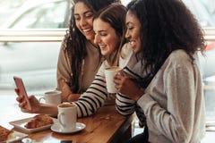Φίλοι που κάθονται σε έναν καφέ που εξετάζει το κινητό τηλέφωνο Στοκ εικόνες με δικαίωμα ελεύθερης χρήσης
