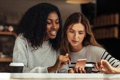 Φίλοι που κάθονται σε έναν καφέ που εξετάζει το κινητό τηλέφωνο Στοκ Φωτογραφίες