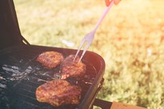 Φίλοι που κάνουν τη σχάρα και που έχουν το μεσημεριανό γεύμα στη φύση Ζεύγος που έχει τη διασκέδαση τρώγοντας και πίνοντας pic-ni Στοκ εικόνες με δικαίωμα ελεύθερης χρήσης