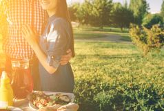 Φίλοι που κάνουν τη σχάρα και που έχουν το μεσημεριανό γεύμα στη φύση Ζεύγος που έχει τη διασκέδαση τρώγοντας και πίνοντας pic-ni Στοκ φωτογραφία με δικαίωμα ελεύθερης χρήσης
