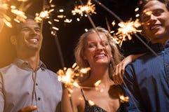 Φίλοι που κρατούν τα sparklers πυράκτωσης στο κόμμα Στοκ Εικόνες