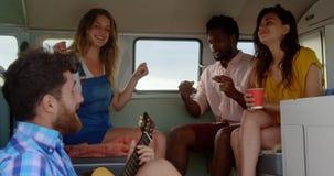 Φίλοι που παίζουν την κιθάρα και που τραγουδούν το τραγούδι 4k απόθεμα βίντεο