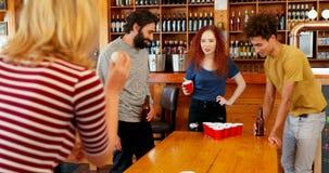 Φίλοι που παίζουν την μπύρα pong στον πίνακα στο φραγμό 4k απόθεμα βίντεο