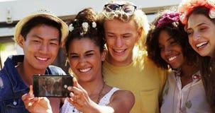 Φίλοι που παίρνουν selfie με το κινητό τηλέφωνο στο πάρκο 4k απόθεμα βίντεο