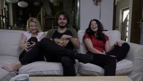 Φίλοι που προσέχουν μια κωμωδία στη συσκευή TV εγχώριων κινηματογράφων και που τρώνε popcorn και που γελούν σκληρά απόθεμα βίντεο