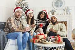 Φίλοι που προσέχουν τον κινηματογράφο και που έχουν τη διασκέδαση στη Παραμονή Χριστουγέννων στοκ εικόνες με δικαίωμα ελεύθερης χρήσης