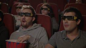 Φίλοι που προσέχουν τον τρισδιάστατο κινηματογράφο στον κινηματογράφο τρισδιάστατη ψυχαγωγία κινηματογράφων concep απόθεμα βίντεο