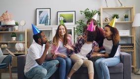 Φίλοι που συγχαίρουν το δυστυχισμένο κορίτσι φέρνοντας κέικ τραγουδιού γενεθλίων στο τραγουδώντας απόθεμα βίντεο