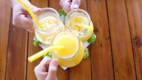 Φίλοι που τα γυαλιά με το χυμό από πορτοκάλι Κορυφή της άποψης κίνηση αργή 3840x2160 απόθεμα βίντεο