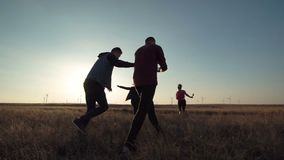 Φίλοι που τρέχουν προς το αιολικό πάρκο στο ηλιοβασίλεμα απόθεμα βίντεο