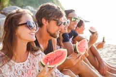 Φίλοι που τρώνε το καρπούζι στην παραλία στοκ εικόνα
