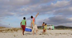 Φίλοι που φέρνουν το πιό δροσερό κιβώτιο στην παραλία 4k απόθεμα βίντεο