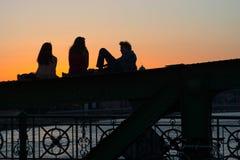 Φίλοι που χαλαρώνουν και που μιλούν υπαίθρια Στοκ Εικόνα